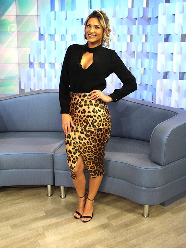 Lívia Andrade usando saia de oncinha fendada e blusa preta decotada