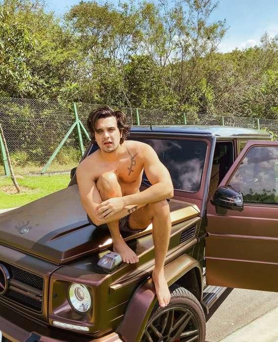 Luan Santana sentado no capô do carro sem camisa